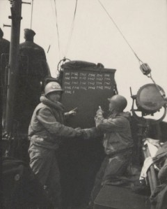 """Crew of CG-16 pointing to the tally board of 126 rescued soldiers.""  Photo courtesy of Terry Hannigan. (NOT AN OFFICIAL USCG PHOTOGRAPH)"