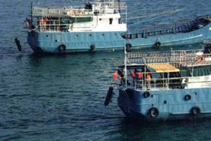 A photo published in a report on Chinese mine warfare by the U.S. Naval War College shows Chinese civilian fishing vessels practicing deploying sea mines at a naval base in Sanya in 2004. —Courtesy of U.S. government
